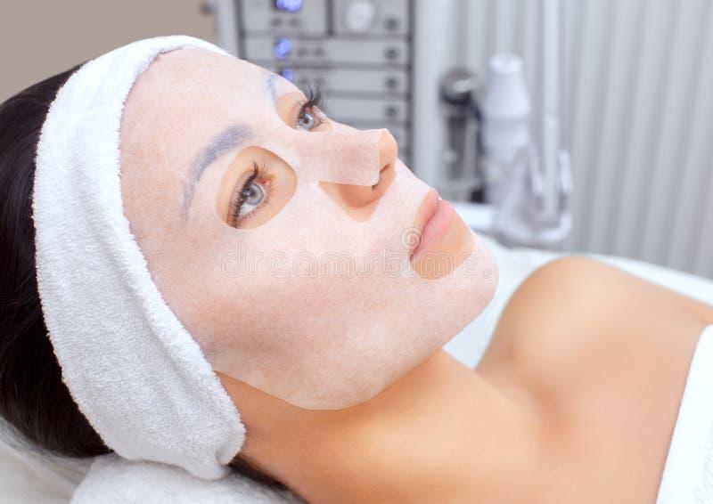 Cosmetologist voor procedure die om de huid te reinigen en te bevochtigen, een bladmasker toepassen op het gezicht stock afbeelding
