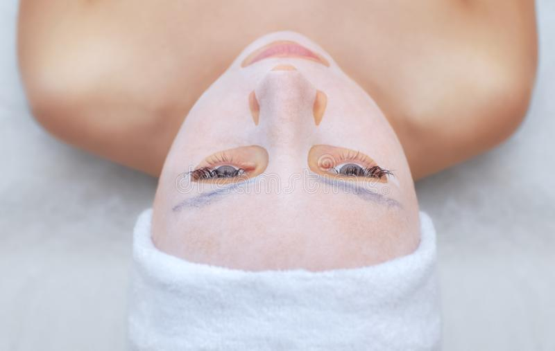 Cosmetologist voor procedure die om de huid te reinigen en te bevochtigen, een bladmasker toepassen op het gezicht van een jonge  stock foto's
