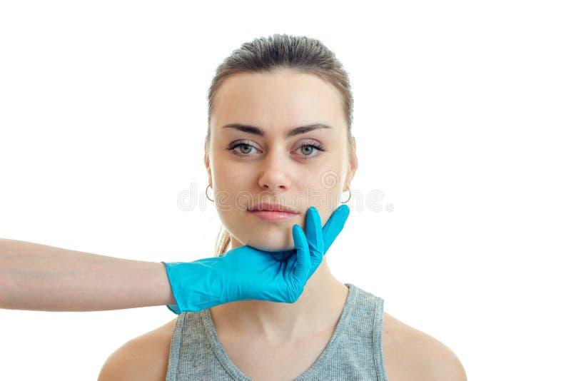 Cosmetologist w błękitnej rękawiczce utrzymuje podbródek od młodego pięknego dziewczyny zakończenia obrazy royalty free