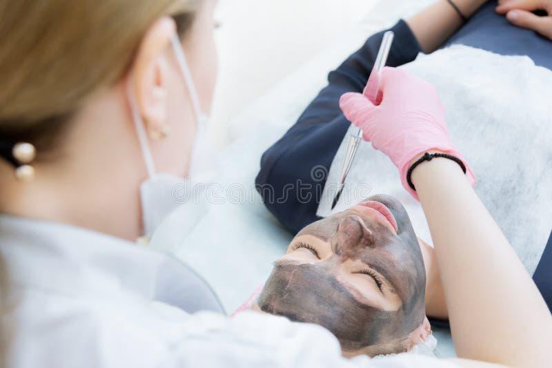 Cosmetologist w różowych rękawiczkach z muśnięciem stosuje węgiel maskę dla strugać na twarzy młoda dziewczyna w a zdjęcia royalty free