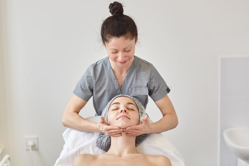 Cosmetologist wears gray gown massaging patient face. Young woman with naked shoulders and dresses madical cap has beauty facial royalty free stock photography