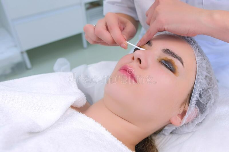 Cosmetologist wiping solution from girl`s lashes on lift lamination procedure. Cosmetologist wiping solution from girl`s lashes using cotton stick on lift royalty free stock photo