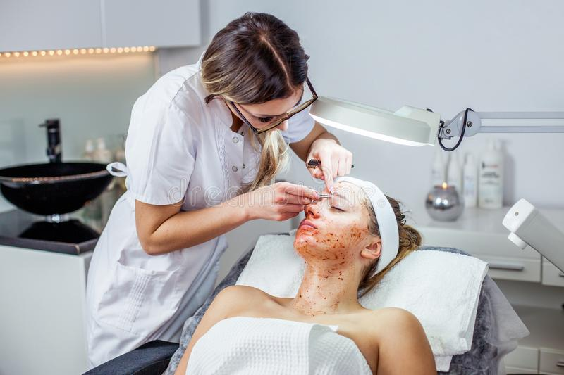 Cosmetologist woman is doing eyebrow modeling for woman / girl by wax for epilation. Cosmetological clinic. Healthcare. Cosmetologist women is doing eyebrow royalty free stock image