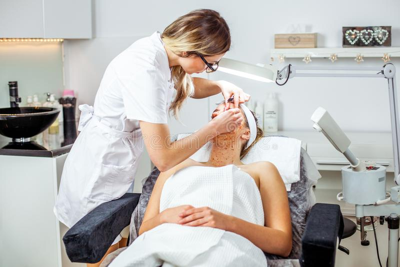 Cosmetologist woman is doing eyebrow modeling for woman / girl by wax for epilation. Cosmetological clinic. Healthcare. Cosmetologist women is doing eyebrow royalty free stock photo