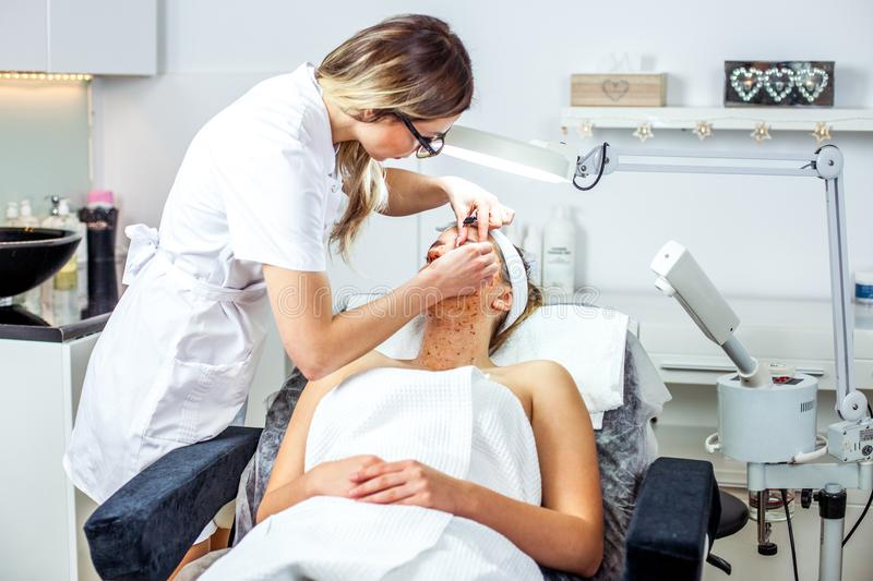 Cosmetologist woman is doing eyebrow modeling for woman / girl by wax for epilation. Cosmetological clinic. Healthcare. Cosmetologist women is doing eyebrow royalty free stock photos
