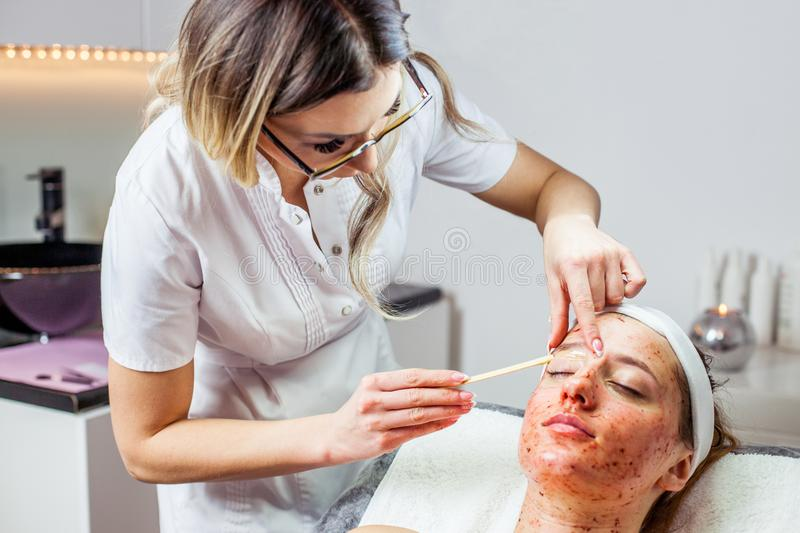 Cosmetologist woman is doing eyebrow modeling for woman / girl by wax for epilation. Cosmetological clinic. Healthcare. Cosmetologist women is doing eyebrow stock photos
