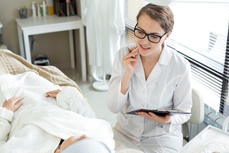 Cosmetologist Working med klienten royaltyfri bild