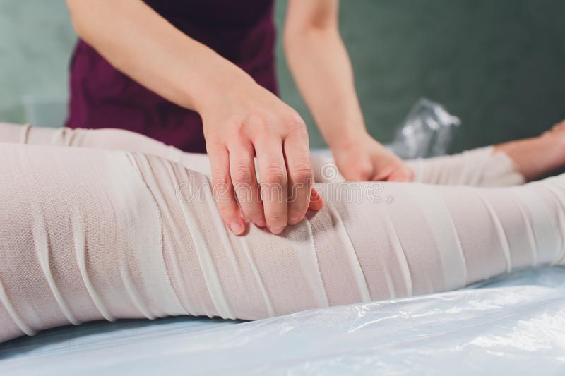 The cosmetologist wraps the leg of the customer. Anti-cellulite procedure-STYX wrap. royalty free stock images