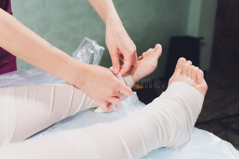 The cosmetologist wraps the leg of the customer. Anti-cellulite procedure-STYX wrap. stock photos