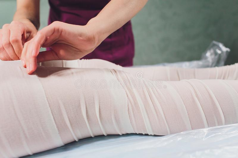 The cosmetologist wraps the leg of the customer. Anti-cellulite procedure-STYX wrap. stock images