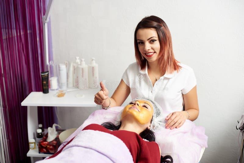 Cosmetologist zeigt sich Daumen beim Geben einer Gesichtsbehandlung als Anwenden einer Goldmaske an einem Kunden eines Schönheits lizenzfreie stockfotos
