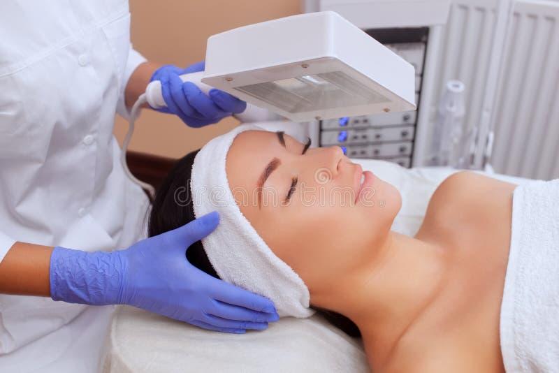 Cosmetologisten använder den Wood lampan för den detaljerade diagnosen av hudvillkoret royaltyfri fotografi