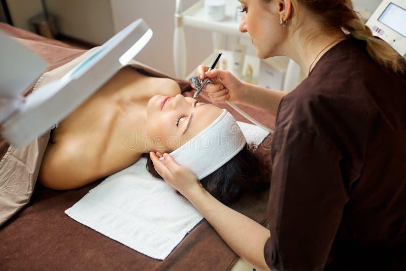 Cosmetologisten gör en kvinna ett tillvägagångssätt bio oxideringterapi arkivfoton