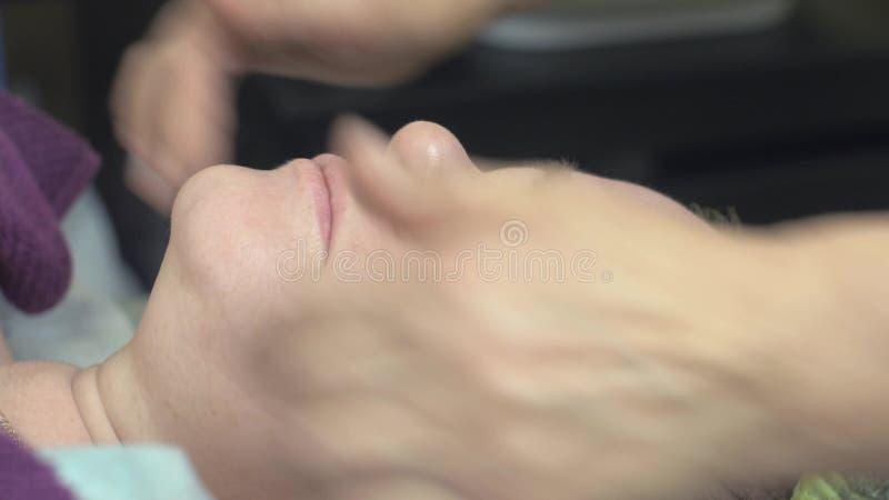 Cosmetologisten gör massageframsidan den tjocka kvinnan i skönhetsalong pressing Anti-ålder arkivfilmer