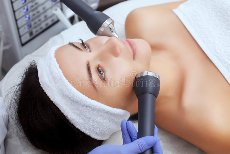 Cosmetologisten gör tillvägagångssättet en ultraljuds- lokalvård av den ansikts- huden av en härlig ung kvinna i en skönhetsalong royaltyfri foto