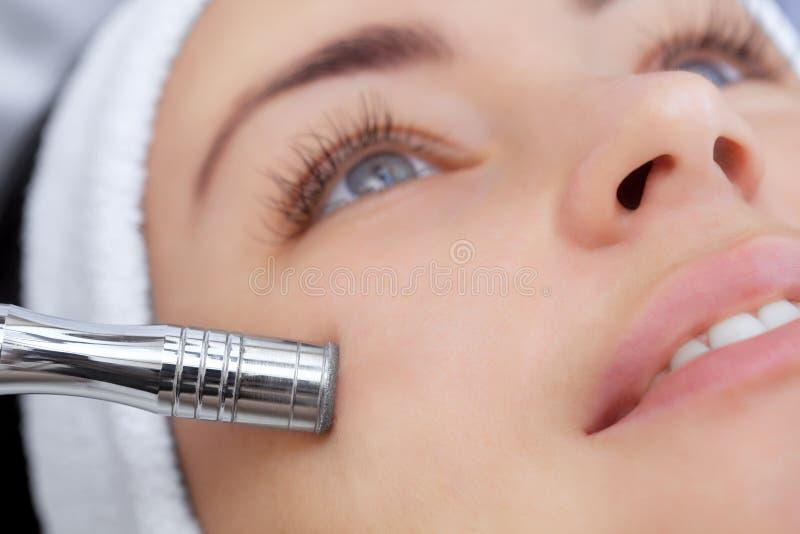 Cosmetologisten gör tillvägagångssättet Microdermabrasion av den ansikts- huden av en härlig ung kvinna fotografering för bildbyråer