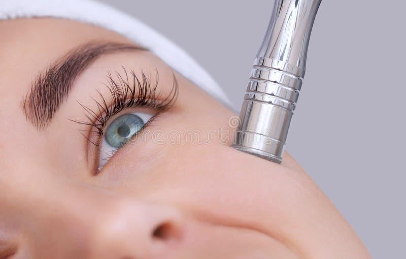 Cosmetologisten gör tillvägagångssättet Microdermabrasion av den ansikts- huden av en härlig ung kvinna i en skönhetsalong arkivbild