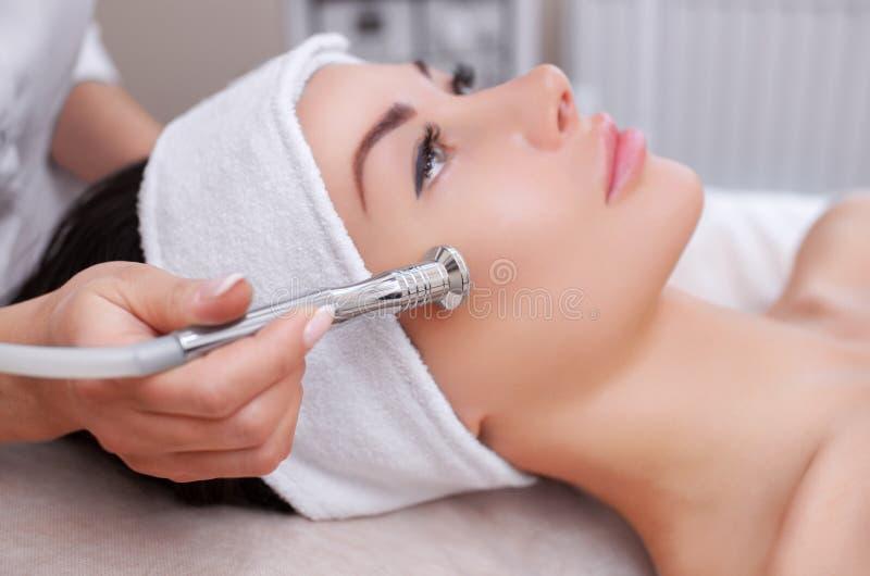 Cosmetologisten gör tillvägagångssättet Microdermabrasion av den ansikts- huden av en härlig ung kvinna i en skönhetsalong arkivbilder
