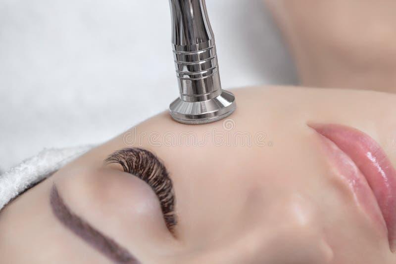 Cosmetologisten gör tillvägagångssättet Microdermabrasion av den ansikts- huden av en härlig ung kvinna i en skönhetsalong royaltyfri foto