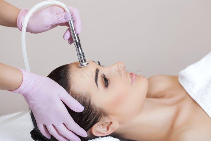 Cosmetologisten gör tillvägagångssättet Microdermabrasion av den ansikts- huden av en härlig ung kvinna i en skönhetsalong royaltyfria bilder