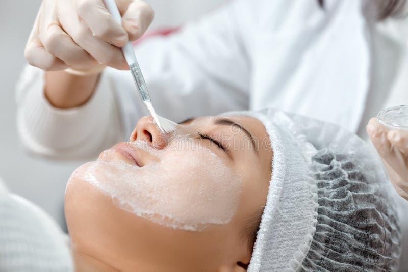 Cosmetologisten sätter en maskering på framsidan royaltyfri fotografi