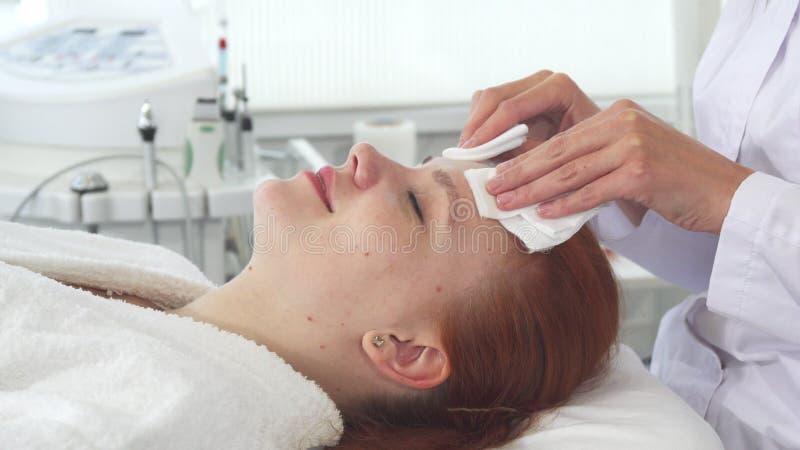 Cosmetologisten torkar framsidan för klient` s med servetter arkivbilder