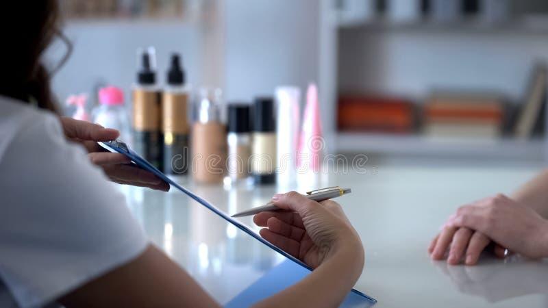 Cosmetologistfüllungs-Kundenkarte vor der Ernennung von den Verfahren, bitten um Zeichen stockfoto