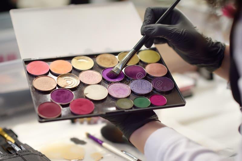 Cosmetologisthänder med paletten för ögonskugga på närbilden för skönhetsalong Borstehandlagpigment på den färgrika ögonskuggapal royaltyfri bild