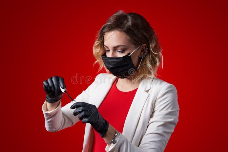 Cosmetologistwijfje zwarte kosmetische rubberhandschoenen dragen en masker die hulpmiddelen voorbereiden royalty-vrije stock fotografie