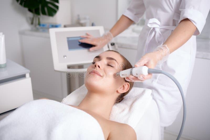 Cosmetologo abile che fa procedura del facial di ultrasuono fotografie stock libere da diritti