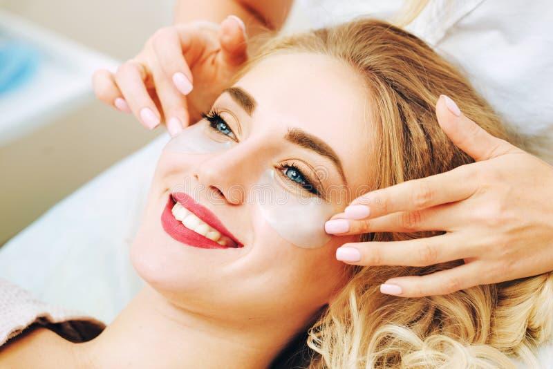 Cosmetologo che applaying i cuscinetti antinvecchiamento del gel dell'occhio immagini stock