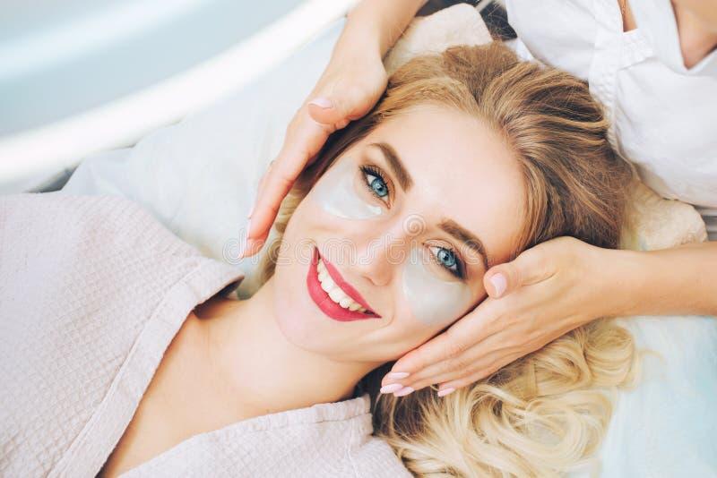 Cosmetologo che applaying i cuscinetti antinvecchiamento del gel dell'occhio immagini stock libere da diritti