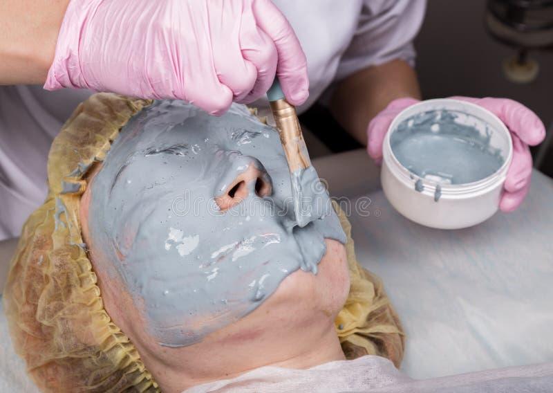 Cosmetologo che applica maschera facciale alla pelle di problema giovane donna che ha procedura di pulizia del fronte immagini stock libere da diritti