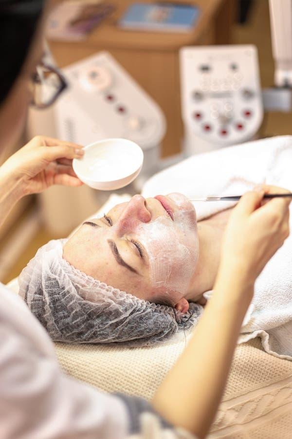 Cosmetologo che applica maschera sul fronte del cliente nel salone della stazione termale fotografie stock