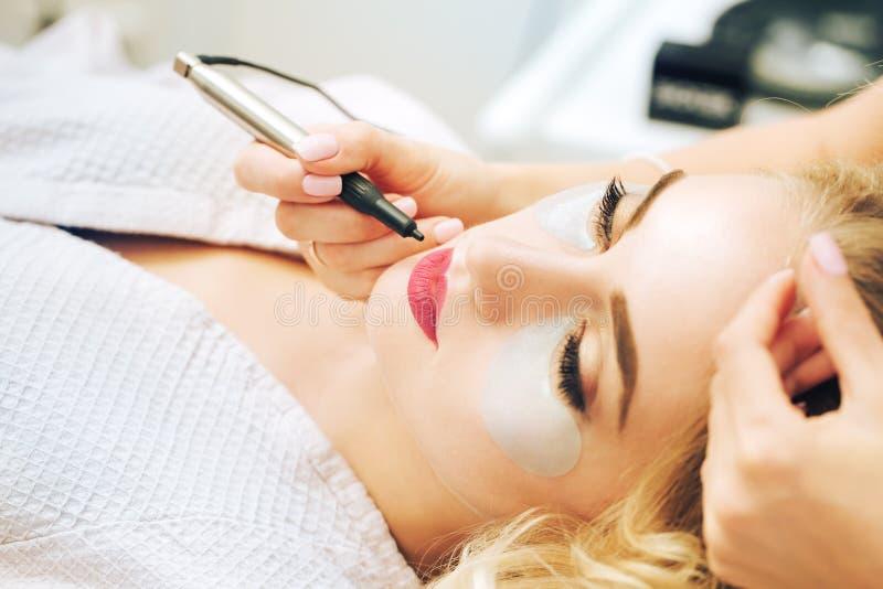 Cosmetologo che applica trucco permanente sulle labbra immagine stock