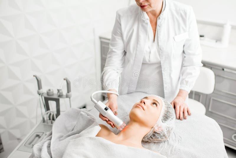 Cosmetologo senior della donna durante la procedura immagine stock