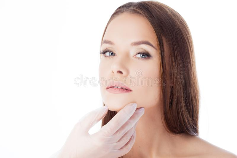 Cosmetology and aesthetic surgery. Portrait of a young attractive woman, clean skin. Gloved hands touching face, isolated on white royalty free stock photography