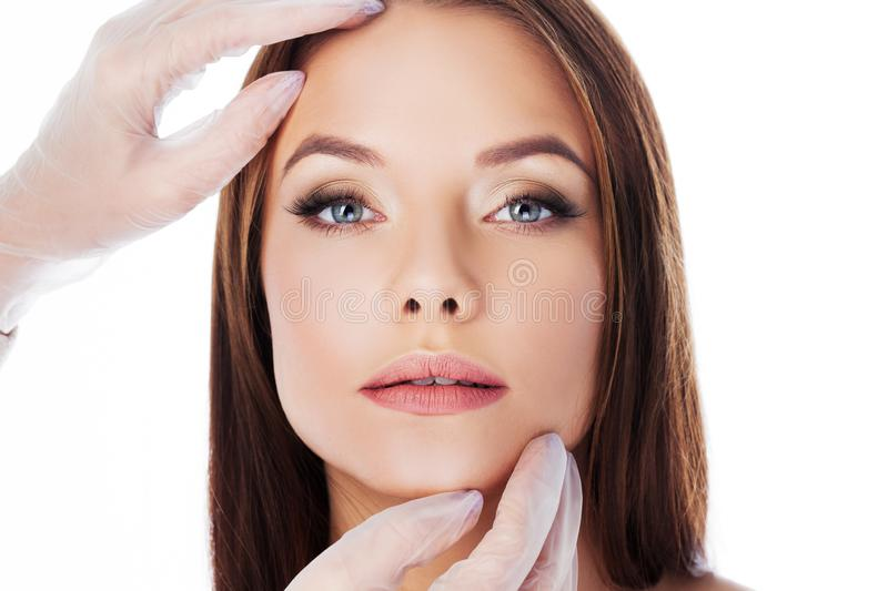 Cosmetology and aesthetic surgery. Portrait of a young attractive woman, clean skin and perfect proportions. Gloved hands touching face, isolated on white royalty free stock image