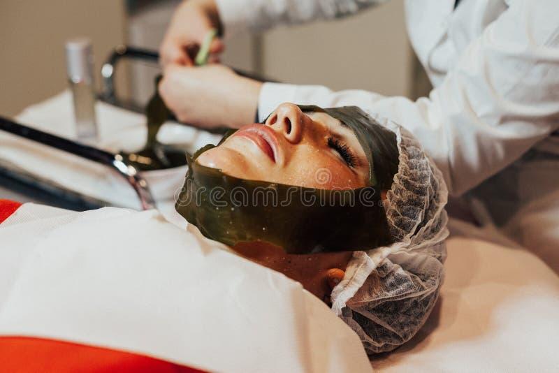 Cosmetology. Algae face mask. Woman on seaweed wrap royalty free stock image