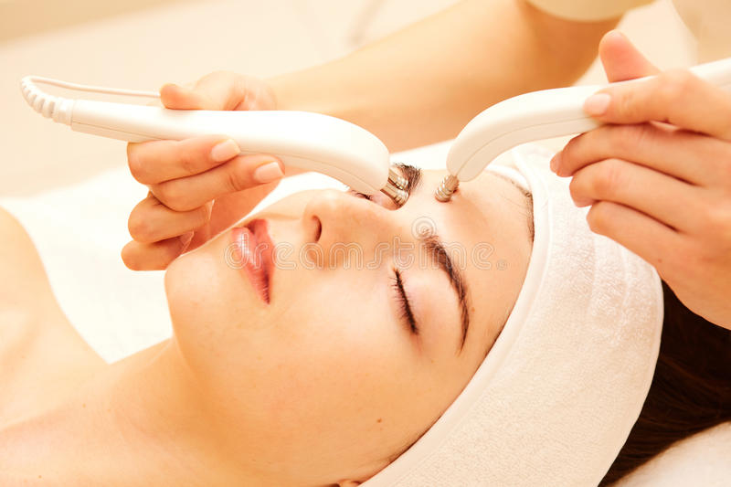 Cosmetology. Beautiful Woman At Spa Clinic Receiving Stimulating Electric Facial Treatment From Therapist. Closeup Of royalty free stock photography