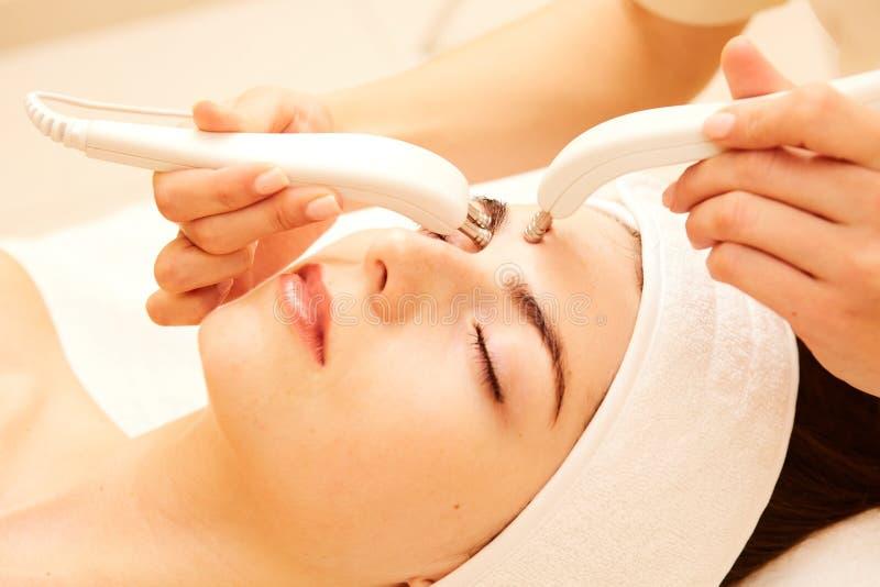 cosmetology Bella donna alla clinica della stazione termale che riceve trattamento facciale elettrico di stimolazione dal terapis fotografia stock libera da diritti
