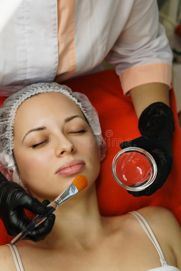 Cosmetology. Cosmetologist applies a cosmetic conductive gel on the face of the client. Anti-aging treatments royalty free stock photography