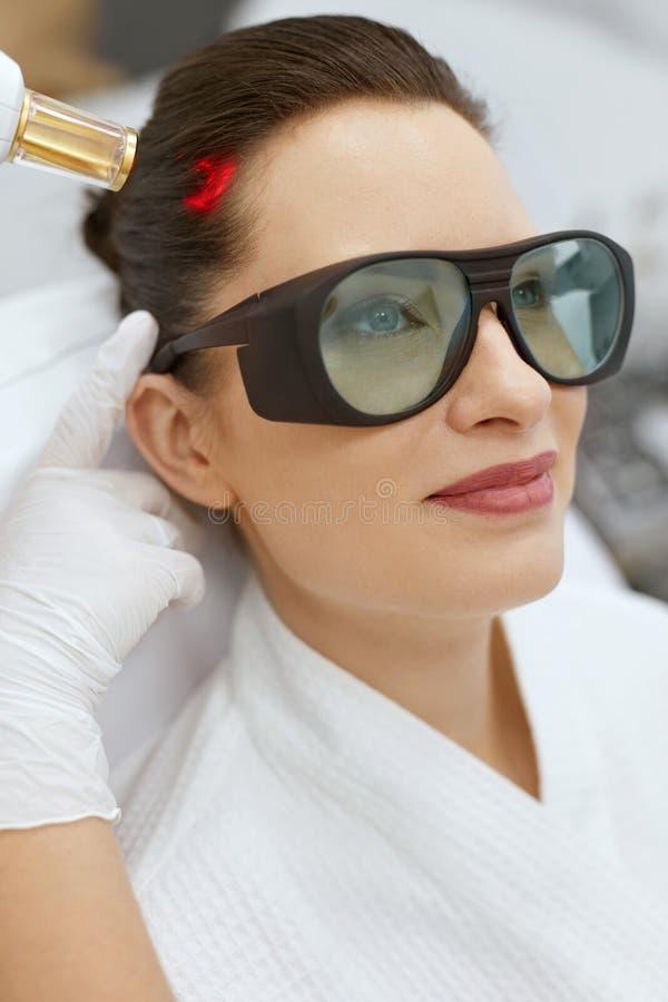 cosmetology Donna al trattamento di stimolazione del laser di crescita dei capelli immagini stock