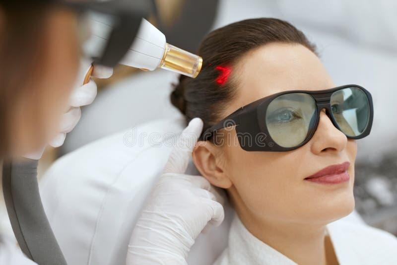 cosmetology Kvinna på behandling för stimulans för hårtillväxtlaser arkivfoto