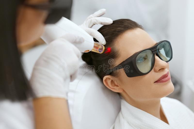 cosmetology Kvinna på behandling för stimulans för hårtillväxtlaser arkivbild