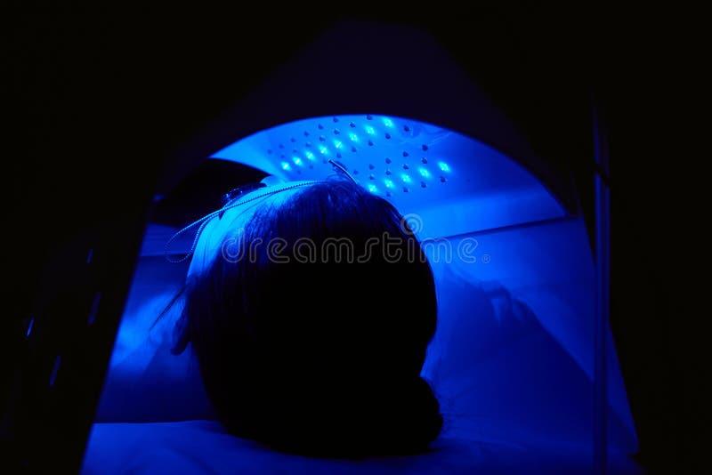 cosmetology Kvinnaframsida på rött ljusbehandling på skönhetkliniken arkivbild
