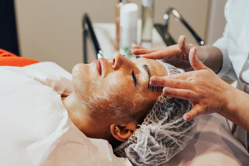 Cosmetology. Woman is having face mask in cosmetology cabinet. stock images