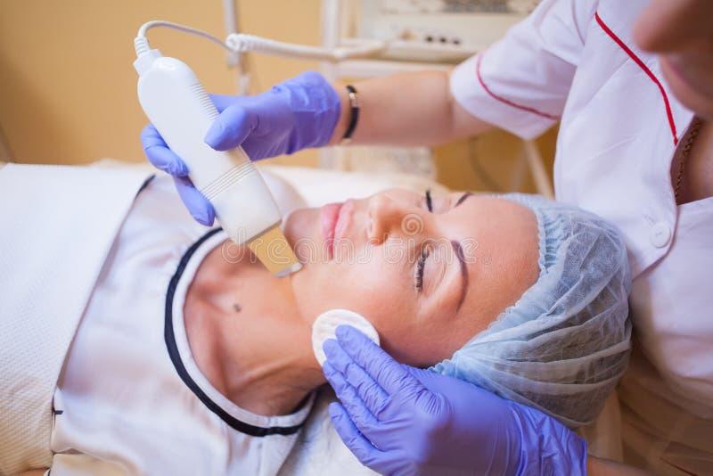 Cosmetologydoktor lässt das Verfahren eine Frau Reinigung gegenüberstellen stockfoto