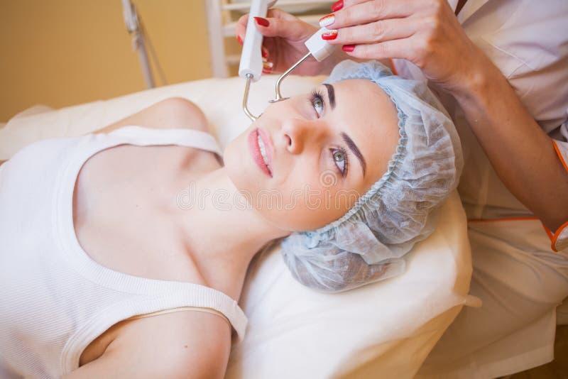 Cosmetologydoktorn gör tillvägagångssättet en kvinna att vända mot lokalvård royaltyfria bilder