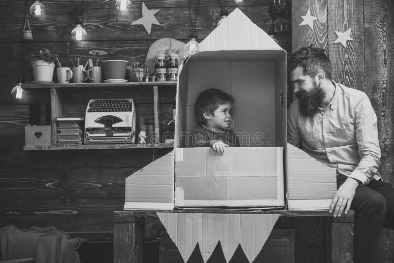 Cosmonauta lindo del juego del muchacho del niño, astronauta El niño feliz se sienta en cohete hecho a mano de la cartulina Juego imagen de archivo